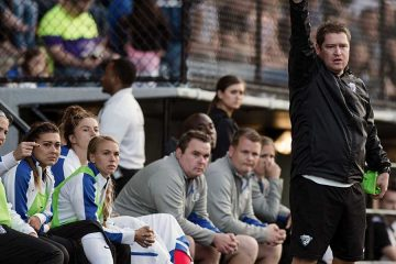 Matt Beard, head coach of the Boston Breakers, in fron of the team bench. by Mike Gridley