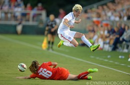 Megan Rapinoe avoids a sliding Fabienne Humm during the friendly between the United States and Switzerland on August 20, 2014, in Cary, N.C.