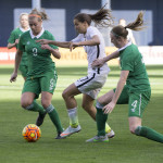 Tobin Heath tries to maneuver past Ruesha Littlejohn (9) and Louise Quinn (4)