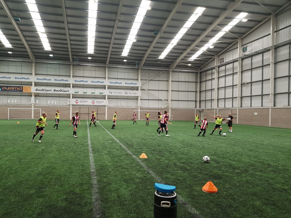 The team warms-up on the academy's full 3G indoor pitch ahead of their first match together. (Photo: Rich Laverty)